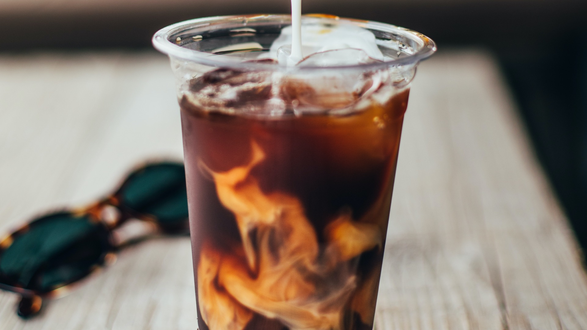 Pouring milk into a cold brew from a Columbia, South Carolina coffee shop