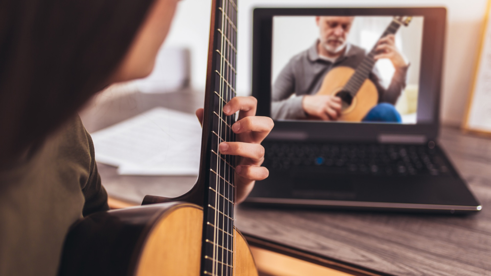 Woman with guitar sitting in front of laptop, taking online music lessons in Columbia